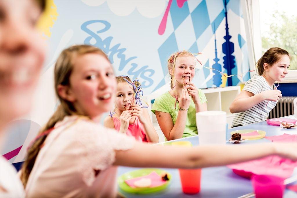 Mädchen sitzen am Geburtstagstisch