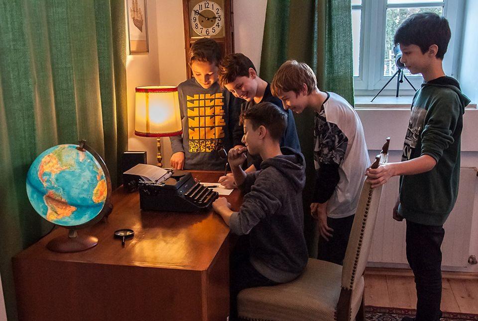 Jungs stehend und sitzen vor einer Schreibmaschine
