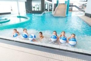Kinder mit Ball im Schwimmbecken