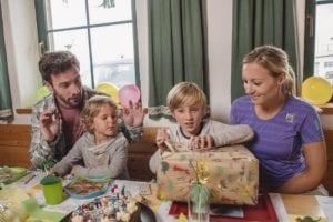 Junge packt Geschenk aus mit seiner Familie